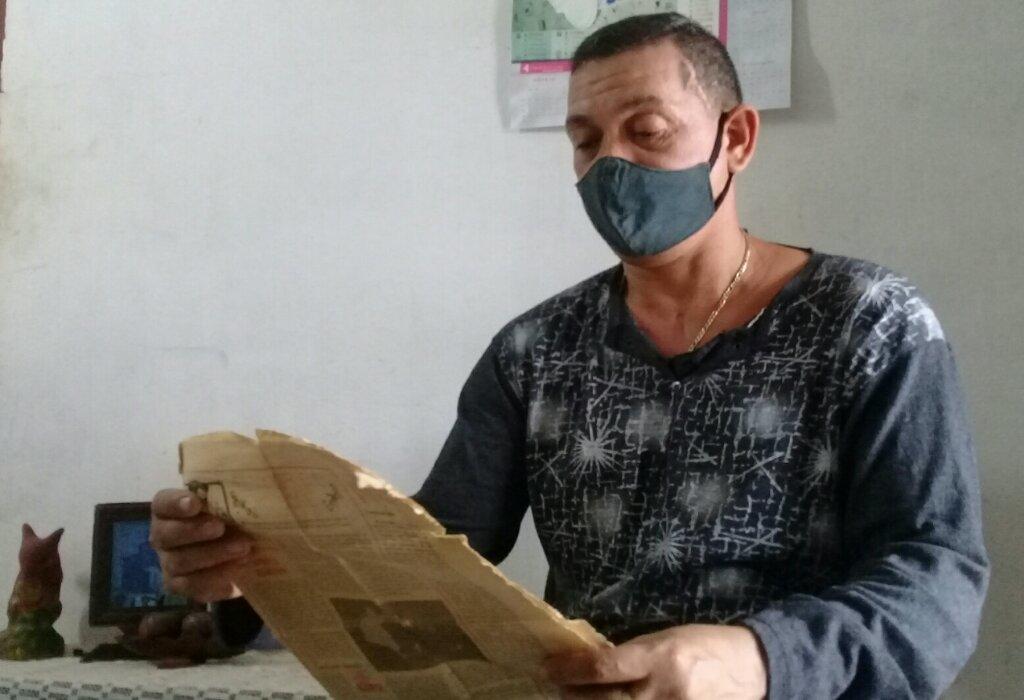 En sus manos las amarillentas páginas del periódico avileño Invasor donde se narró lo sucedido aquel febrero de 1997 //Foto Eliexer Pelaez Pacheco